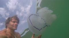 Young man watching the jellyfish (Rhizostoma pulmo). Underwater view Stock Footage