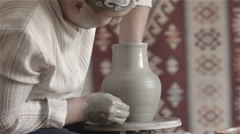 Man working on pottery wheel, shaping a clay pot Stock Footage