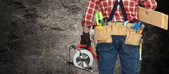 Builder handyman with electric saw. Stock Photos