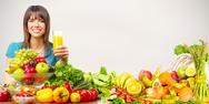 Young healthy woman with orange juice and fruits. Stock Photos