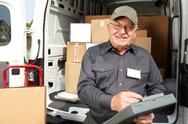 Mature delivery man with a parcel. Stock Photos