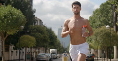 Man Jogging in Cityscape takes sip from unmarked water bottle. Stock Footage