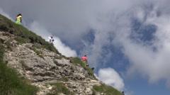 Tourists descending on a narrow  alpine path Stock Footage