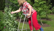 Woman with broken ankle walks with zimmer frame Stock Footage