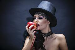 Halloween. Fashion portrait of witch or night vampire woman with  red apple.  Stock Photos
