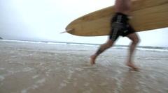 Mature Surfer Dude Running Through the Breaking Waves. Stock Footage