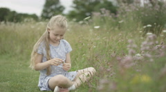 4K Little girl playing alone in the countryside on a summer day Stock Footage