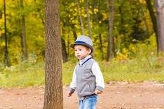 Little baby boy walking in colorful autumn park Stock Photos