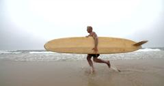 Surfer Dude Running Along Ocean Edge. Stock Footage