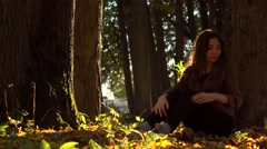 Beautiful brunette girl with picnic basket sitting under the tree in autumn Stock Footage