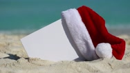 Santa Claus Hat and white blank placard at beach on sea background Stock Footage