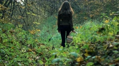 Slender young woman in a brown jacket walking through the forest holding a Stock Footage