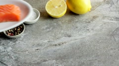 A piece of fresh salmon on a white plate with Lemon, salt and pepper. Stock Footage