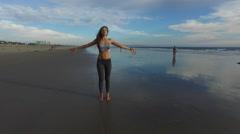 A beautiful woman practicing yoga on the beach in Santa Monica, California, USA, Stock Footage