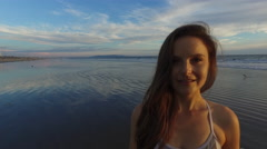 A beautiful young woman circling the camera and flirting on the beach in Santa Stock Footage