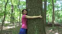 Woman hugging a tree trunk in the woods smiling.Green environmental concept 4k Stock Footage