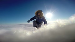 Little boy wearing winter clothes ploughs through snowy desert during a storm Stock Footage