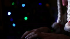 Man wearing funny Santa hat with white plaits writing e-mail near Christmas tree Stock Footage