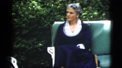 1952: a woman and a man, both in very formal suits, talking in a garden area Stock Footage