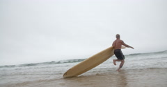 Mature Surf Dude Runs Into the Ocean Dragging his Longboard into the Waves. Stock Footage