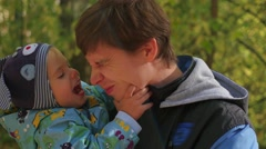 Young father tenderly playing with baby in the autumn Park closeup Stock Footage