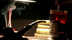 Night study interior: person mixes sugar in a teacup, tobacco pipe smoke whirls Stock Footage