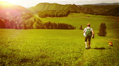 A man with his beagle run down the green hill on a sunny day Stock Footage