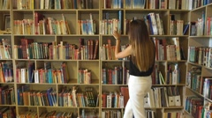 Student girl chooses among the shelves of a book in the library Stock Footage