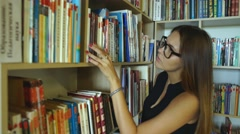 Female student read book in library with bookshelf as background Stock Footage