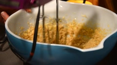 A closeup rack focus shot of a person blending and beating cookie dough Stock Footage