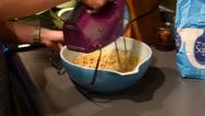 Rack focus shot of a woman beating eggs and flower into a bowl Stock Footage