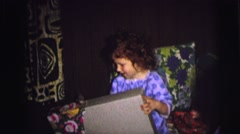 1974: a little girl in pajamas opening the wrapping on a christmas gift CAMDEN Stock Footage