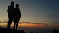 Couple standing on the outcrop on a windy evening watching sunset Stock Footage