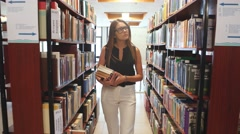 Education and school concept - happy student girl or young woman with book in Stock Footage
