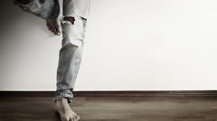 Man stands leaned towards the wall wearing ripped jeans and taps with his foot Stock Footage