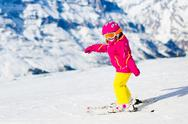 Little child skiing in the mountains Stock Photos