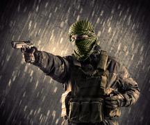 Armed terrorist man with mask on rainy background Stock Photos