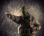 Armed terrorist man with mask on rainy background Stock Photos