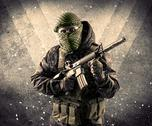 Portrait of a dangerous masked armed soldier with grungy background Stock Photos