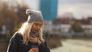 Beautiful young woman with a cup of coffee in the autumn city. Warmed by hot Stock Footage