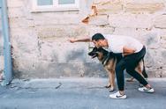 Man and dog posing on the street Stock Photos