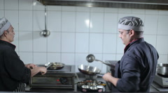 Two cooks are preparing the dishes at the kitchen Stock Footage