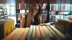 Serious girl student reading a book in the library between the shelves Stock Footage