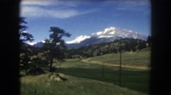 1962: green grass, trees, and snow covered mountains are seen  Stock Footage