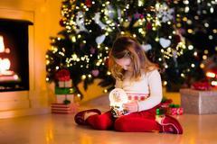 Little girl holding snow globe under Christmas tree Stock Photos