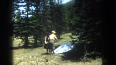 1962: two women outdoors, throwing something at the camera and then pulling pine Stock Footage