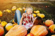 Mother and daughter lie between pumpkins Stock Photos