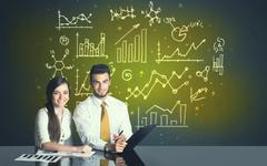 Business couple with business diagrams Stock Photos