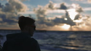 Young man Watching the seagulls sunset on the sea Stock Footage