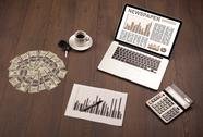 Business laptop with stock market report on wooden desk Stock Photos